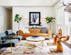 Glam living room with a leather sofa, velvet armchairs, and a pink area rug