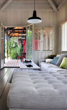 I love the idea of many sofas along a wall that can double as sleeping space