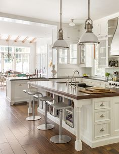 Two Large Country Industrial Pendants illuminate a white beadboard kitchen island with turned legs fitted with cookbook shelves and topped with butcher block framing a black apron sink and deck-mount faucet lined with LEM Piston Barstools. Kitchen Redo, New Kitchen, Kitchen Dining, Kitchen Remodel, Kitchen Island, Kitchen Ideas, Country Kitchen Farmhouse, Modern Farmhouse Kitchens, White Farmhouse