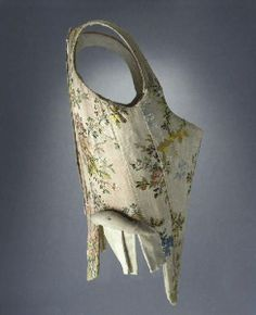 A Pair of Decorated Stays - 1750-60 - Arletan Museum. Side view of stays next door. Small, sausage-like bum roll sewn on side. Fairly long side tabs and longer front point than back. 9 panels. Beautiful shape with the scye sweeping into line with the neckline. Sewn down straps.