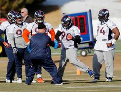 Denver Broncos defensive end Shaun Phillips (90) works on drills as other defensive linemen look on during practice for the football team's NFL playoff game against the San Diego Chargers at the Broncos training facility in Englewood, Colo., on Thursday, Jan. 9, 2014.