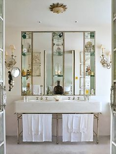 Love the chic Parisian look of this bathroom. the shadowbox mirror, fancy wall sconces, double basin sink and I just noticed the delectable double French doors with crystal handles. ♥ (via Everything Fabulous: Bathroom Inspiration: Double Charm)