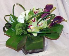 This is a cube vase floral arrangement that features white roses, eggplant miniature calla lilies and green cymbidium orchids with lily grass loops and folded ti leaves. See our entire selection at www.starflor.com. To purchase any of our floral selections, as gifts or décor, please call us at 800.520.8999 or visit our e-commerce portal at www.Starbrightnyc.com. This composition of flowers is generally available for same day delivery in New York City (NYC). SQ199