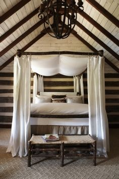 Romantic rustic bedroom with canopy bed, chandelier & exposed beams.