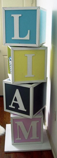 Take large square boxes, add paint colors and letters vertically to spell child's name, insert storage cubes/baskets on inside for baby's stuff- adorable, crafty, space saver & organizer! (glue or nail in place so they can't tip over)