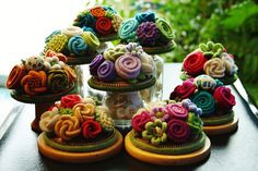 wool flower pincushions.  flowers are arranged in a wooden curtain ring and then attached to a cork coaster.
