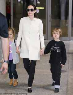 Carry on: Angelina proudly walked on while hand-in-hand with her youngest children with hu...