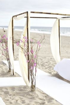 Simple beach wedding arch with white flowing fabric on a bamboo frame and twisty willow branches dotted with blossoms secured in sand filled vases Beach Ceremony, Wedding Ceremony, Our Wedding, Destination Wedding, Dream Wedding, Wedding Arches, Wedding Chuppah, Wedding Canopy, Ceremony Backdrop
