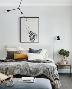 The norsuHOME - Main Bedroom   Photographer: Lisa Cohen Stylist: Beck Simon  Paint: Dulux Terrace White Carpet: Godfrey Hirst  Shutters: Carpet Court  Products:  Menu Franklin Pendant, Rubn Wall lights, Lola Donoghue Zebra Girl print, The Cullin Design Bedhead and Bench seat, norsu cushions, Honey Honey Creations knitted throw, GlobeWest Felix Chair & Henley Side Table (all available at www.norsu.com.au)