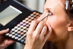 Makeup artist applying eye makeup - Rich Legg/Getty Images