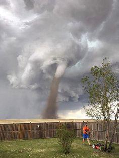 NEOHROŽENÝ ZAHRADNÍK. Kanaďan Theunis Wessels seká trávník u svého domu v Tree Hills v Albertě v okamžiku, kdy se v pozadí točí větrné tornádo. Podle jeho manželky, která snímek pořídila, nebyl vír tak blízko, jak se zdá.