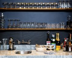 Bar ware storage against a black and slate wall.