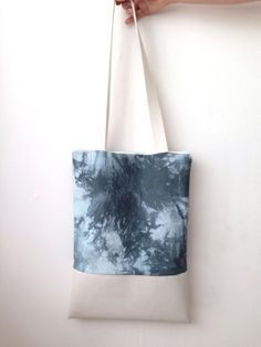 Tie-dye cotton tote bag with faux leather straps and bottom, lined with white cotton.