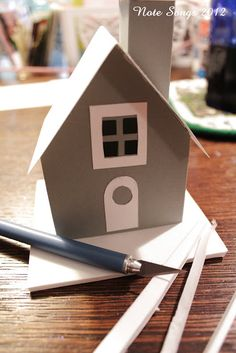 Note Songs: How I Make Glitter Houses step 3-house is gray cardstock. I like to use a different color for the roof so I've chosen white. Score and fold down the center of the roof and your ready to glue it onto the house.