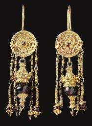 A PAIR OF GREEK GOLD AND GARNET EARRINGS  HELLENISTIC PERIOD, CIRCA LATE 4TH CENTURY B.C.  Each with a pan-shaped disk, the upturned edge formed of two beaded wires framing plain wire, with ropes and plain wire encircling a filigree rosette centered by a garnet in a dog-tooth setting, each disk with a hooked earwire on the reverse, formed into a loop suspending a pendant with an elaborately-capped garnet