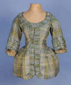 PLAID SILK PET-EN-LAIR JACKET, 18th C. Pale blue, green, cream and purple plaid having rounded front neckline squared in the back above Watteau pleats, short sleeve with bands of self ruching, neck and front trimmed with furbelows, inverted side pleats and linen lining. B-32, W-24, L-24. $600-800.