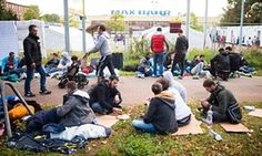 Refugees sit on the grass in front of a refugee shelter in Hamburg