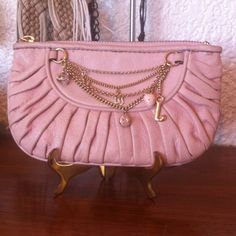 """JUICY COUTURE Pale Pink Leather Wristlet Embellished by charms and chains. All leather. Interior lined in signature fabric. Credit card leather slots/compartments. Zipper pull missing. Slight scuffing. Small stain on one back pleat. L 7.5"""" H 4.5"""" Juicy Couture Bags Clutches & Wristlets"""