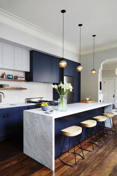 plan de travail ilot central en marbre avec un soubassement peint de même couleur bleu marine que les armoires de cuisine, réchauffé par des accents en bois
