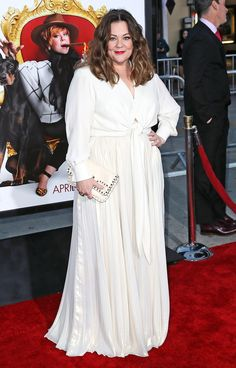 MELISSA MCCARTHY wears a white long-sleeve blouse tied at the waist with a pleated maxi skirt and