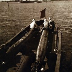 Small boat carries torpedoes to a submarine Photographed by Lieutenant Commander Horace Brisol, TR-15201, May 1945. U.S. Navy Photograph, now in the collections of the National Archives.