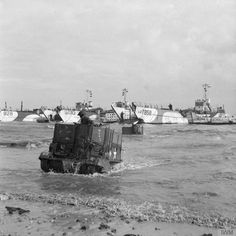 Universal Carriers of 50th Division wade ashore from LCTs on Jig beach, GOLD area. LCT 928, LCT 710, LCT 858 and LCM 244 are visible in the background. The markings on the carrier indicate a vehicle from 1st Dorsetshire Regiment, 231st Brigade