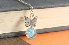 This dazzling sterling butterfly in Angelic Embrace™ sits atop your custom memory glass pearl. It's set with 15 crystal stones on each extended wing.