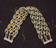 Reversible Cable Knit Bracelet. I started out with a single-strand bracelet and noticed it had a reversible effect. I modified the design and made a triple-row reversible bracelet. The texture and pattern remind me of a cable knit sweater :D Miyuki seed beads in silver, green and yellow, silver-lined bugle beads and magnetic 3-strand clasp.