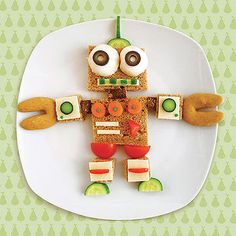 Veggie Robot 1. Make eyeballs from mushroom caps.    2. Create limbs with bread, cheddar cheese, carrots, cucumber, bell pepper, cherry tomatoes, and candy sprinkles.   3. Use crescent-shaped or fortune cookies for hands.  (450 calories, 15g fat)