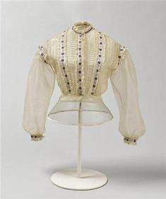1860s body in cotton, silk, white voile trimmed with pintucks, lace, embroidery, and violet faille ribbons (my translation). Domaine de Compiègne.