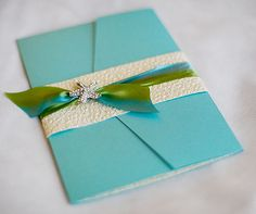 A teal wedding invitation is wrapped in glamorous textured paper and ribbon studded with a starfish.