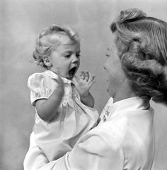 In her new home, Linda Joy claps her hands vigorously and babbles happily as she gets acquainted with her new mother, Mrs. Robert Linville Young, who adopted her.