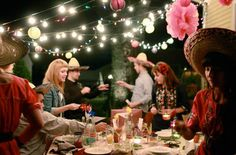 Fiesta Themed Party....Repurposing old glass Coca Cola bottles as vases, setting up a taco bar for a themed dinner, and mixing in colorful tissue paper pom poms with string lights!