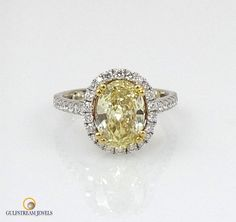 Fancy Yellow Oval Diamond Ring. Certified by GIA 2.03ct Fancy Yellow VS2 set with over .50cts of round brilliant cut in diamond 18kt gold.