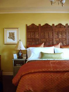A hand-carved Indian Rosewood screen purchased at a flea market adds texture and an ethnic touch to this bedroom. The perfect width for a king-size bed, the four-panel screen was installed directly against the wall above the baseboard to save space. Photo courtesy of Adeeni Design Group