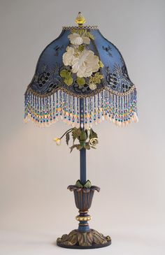 Beautiful antique table base with a spray of metal tole dimensional flowers has been hand painted & holds a Belladonna lampshade. The shade is dyed midnight blue & is covered with a striking antique black & silver net lace & then overlaid with a spray of Edwardian era embroidered white rose appliqués. The shade has hand-beaded fringe in blues, lavender, green & yellow -