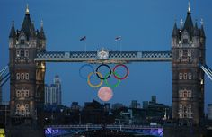 Full moon rises through the Olympic rings at Tower Bridge in London.