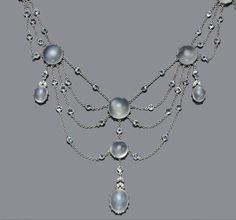 A moonstone, aquamarine and diamond swag necklace  estimated total moonstone weight: 45.40 carats; estimated total aquamarine weight: 4.30 carats; mounted in eighteen karat white gold; length: 16in.
