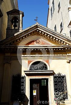 Photo taken in Oderzo in the province of Treviso in the Veneto region (Italy). In the picture you see a small church, illuminated by the sun, squeezed between two homes. On either side of the main entrance there are two windows and a semicircle above the main door protected by a sturdy wrought iron gate. IOLs over the roof and in the shadow you can also see the small bell tower. with a single bell.