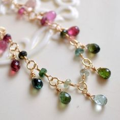 Elegant tourmaline necklace drips with sparkly gemstones in all shades of pink and green. Teardrop-shaped tourmaline stones create the glittery fringe at the front of the necklace, and the fine gold-filled chain complements the stones beautifully. Stones blend from the palest pink on the ends, to deep greens, to soft green in the center. Tiny green gemstones connect the lobster clasp. What a perfect piece to welcome Spring! The length of this necklace is adjustable from approx. 16 1/2-18…