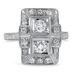 The long, rectangular ring features three bezel set diamonds surrounded by glittering diamond accents, and exudes quintessential 1920s style.