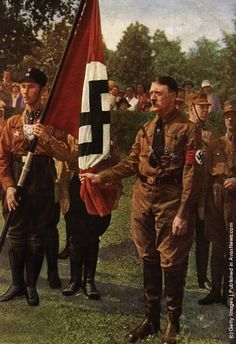 """'Blutfahne' : Adolf Hitler holds the """"Bloodied Standard"""" of the Nazi party at a memorial ceremony for the failed uprising of 9th November 1923, known as the """"Beer Hall Putsch"""". (Photo by Heinrich Hoffmann/Hulton Archive/Getty Images). Circa 1929"""