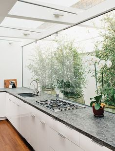This new kitchen borrowed space and light from the original courtyard. The spirit of the courtyard remains with the buffer between the kitchen and the exterior wall. The cabinets are from Ikea, the countertops are quartzite, and the grill top is from Bertazzoni.