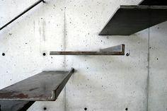 Escalones de chapones metálicos empotrados en muro de hormigón visto