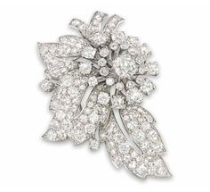 A DIAMOND BROOCH, BY CARTIER   Designed as a flower spray, the old-cut cushion shape diamond centre to twin diamond point petal surround and pavé-set diamond leaf surmount, circa 1935, 4.4cm wide, maker's case  Signed Cartier London