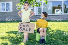 Young girl putting her brother for sale in a garage sale during a summer day royalty-free stock photo Funny Family Christmas Cards, Royalty Free Images, Royalty Free Stock Photos, Garage Sale Signs, Funny Poses, Kids Ties, Girl Tied Up, For Sale Sign, Her Brother