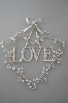 ~ Love ~  heart wreath with twining leaves hung from a bow - this could be done in mostly fabrics, or in metals ... all white as shown, or with pastels introduced ... hmmm