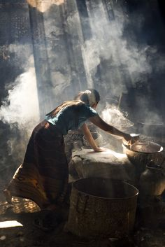 The light in this photograph by Bas Uterwijk (Woman preparing rice crackers in a small hut, Inle Lake, Myanmar)
