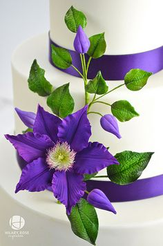 Round Wedding Cakes - Purple gum paste Clematis and buds dusted with Empress Purple to match the ribbon on 3 tier wedding cake.