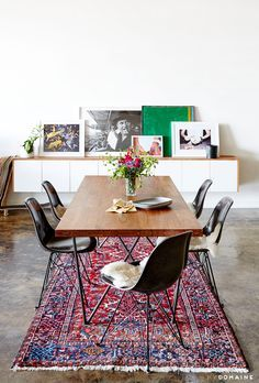 An industrial and modern dining space with leaning artwork, Persian rug, and wood dining table